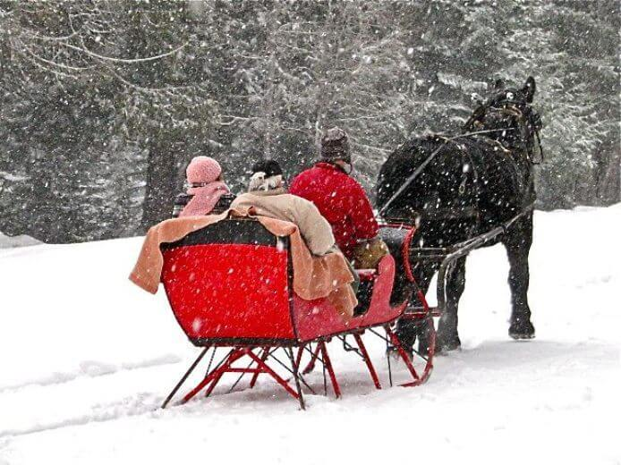 Couple enjoys a winter sleigh ride at Western Pleasure Guest Ranch.