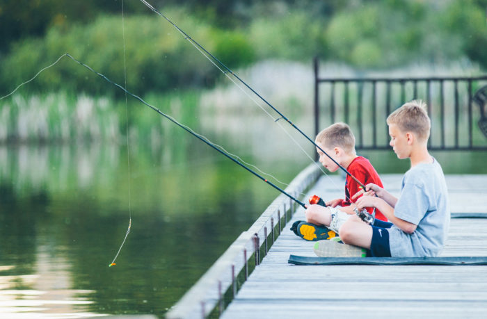 Two kids fishing on a dock.