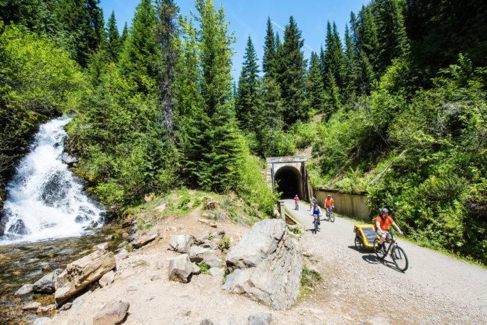 family rides bikes near waterfall