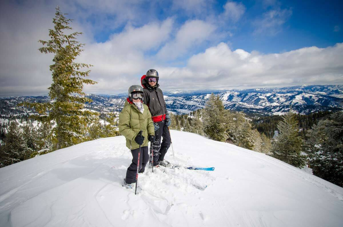 Two skiers posing for a picture on top of a mountain.