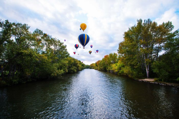 Air balloons floating over a river surrounded by trees.