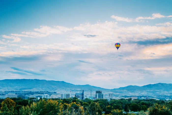 An air balloon floating over a city landscape.