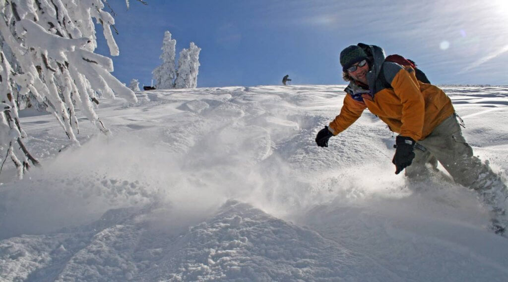 A snowboarder riding down a mountain of snow.