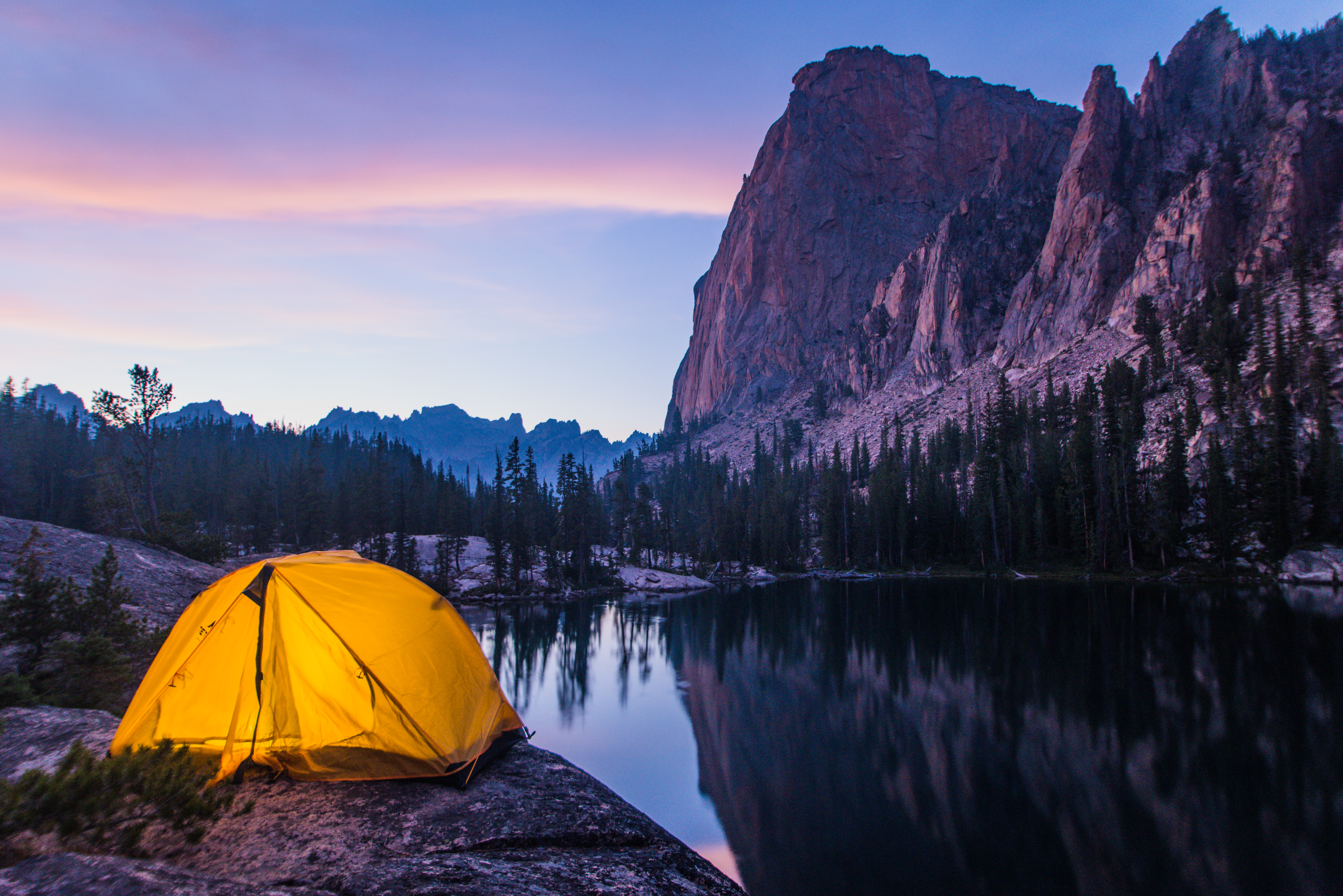 A lit tent beneath a mountainside at night.