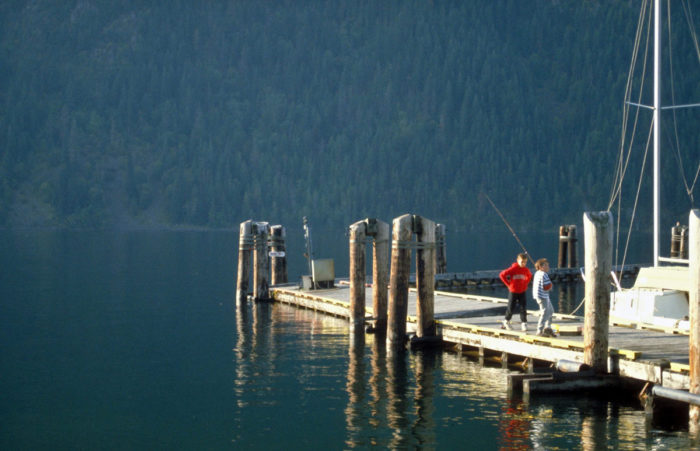 Two people fishing on a dock.