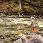 Son fishing rapids from a rock.