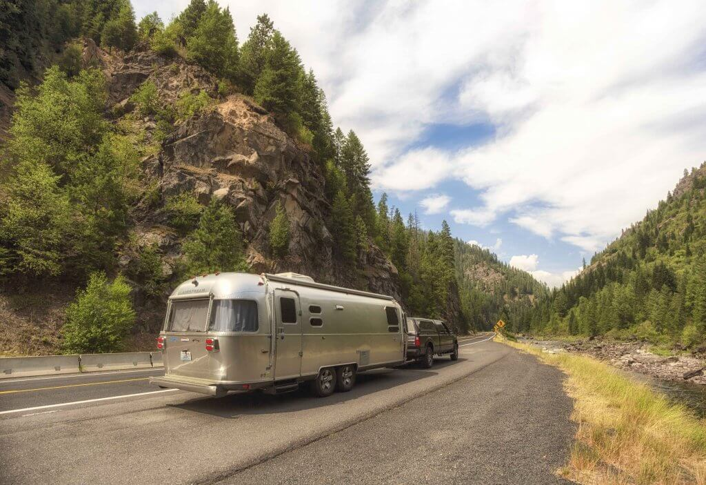 Airstream on the road home with mountain views.