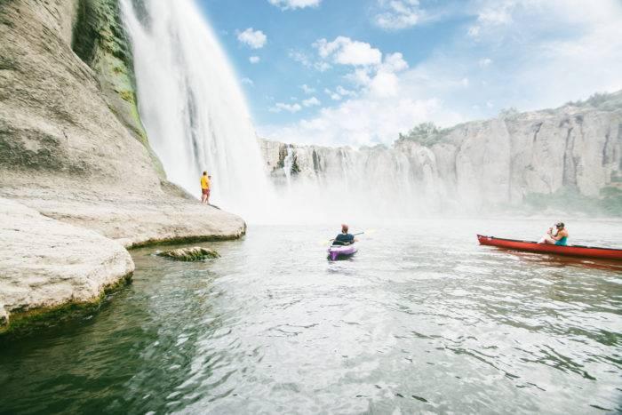 Two kayakers paddling beneath a waterfall.