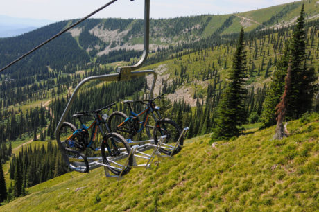 A pair of mountain bikes being transported up a ski lift during the summer.