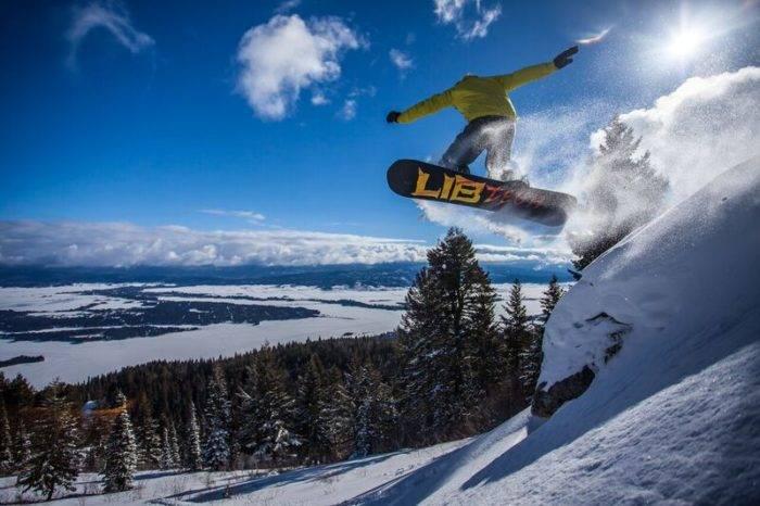 A snowboarder headed down a ski run.