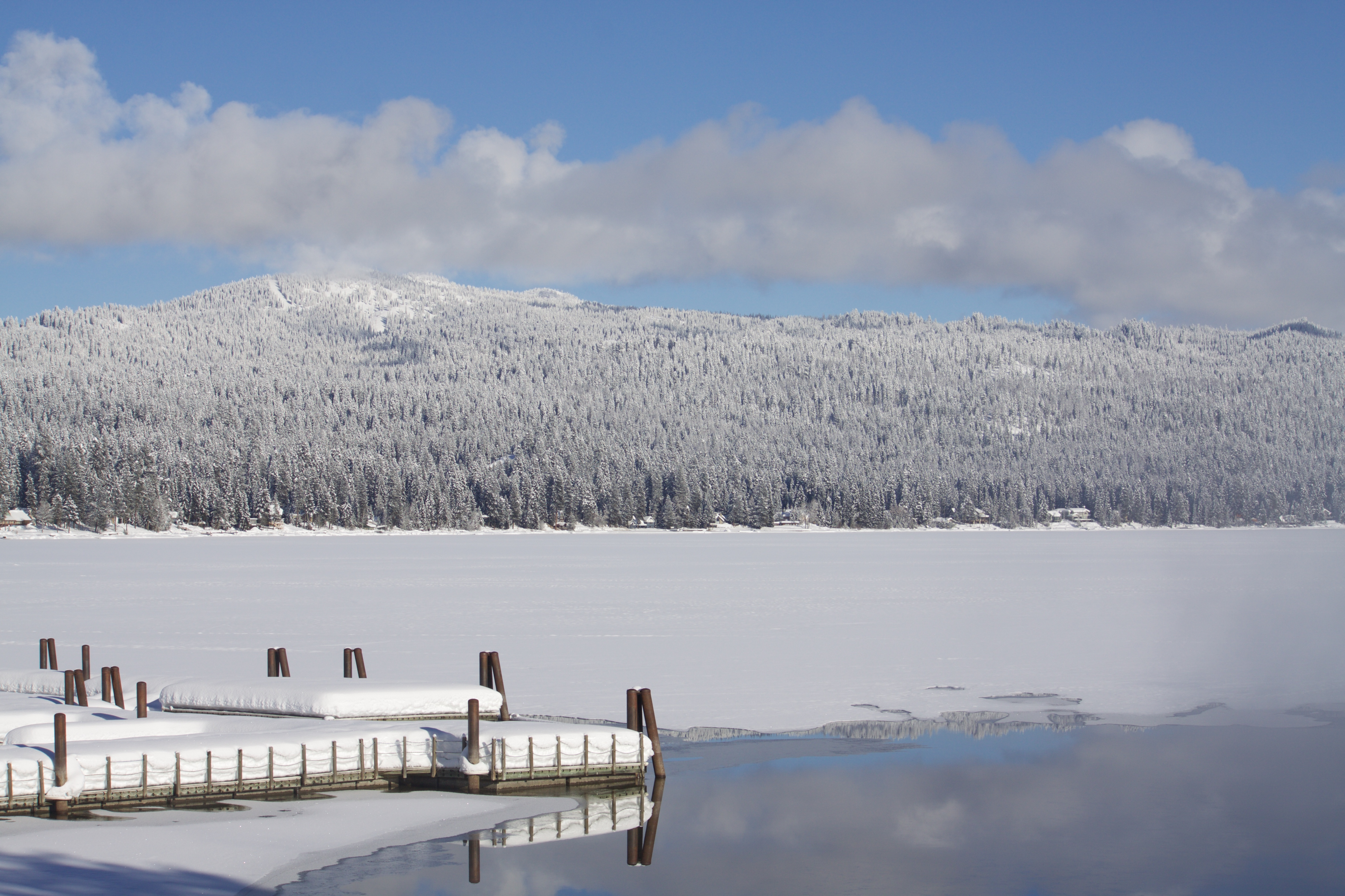 A view of a frozen lake with mountains in the background.