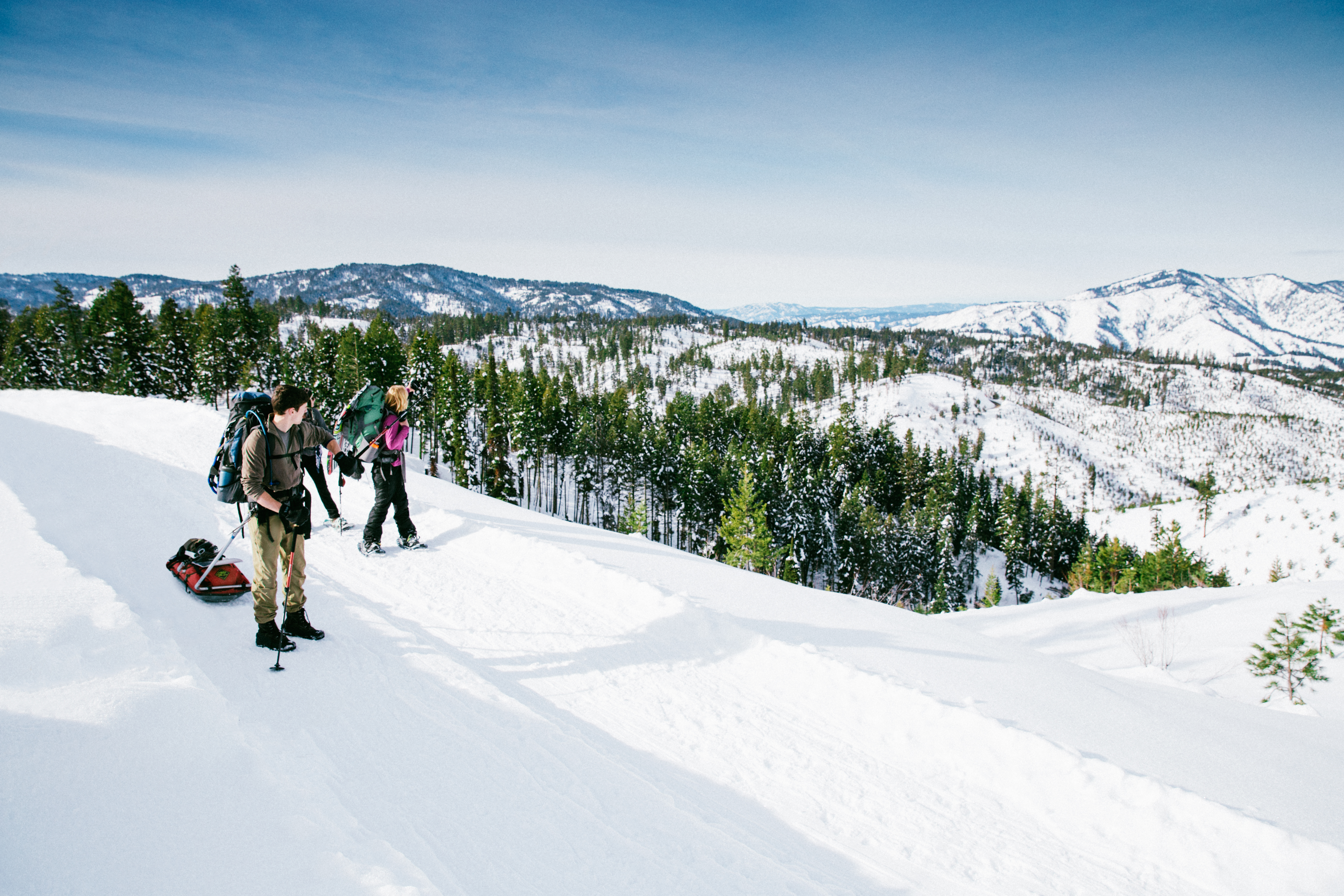 Two people snowshoeing on a mountain.