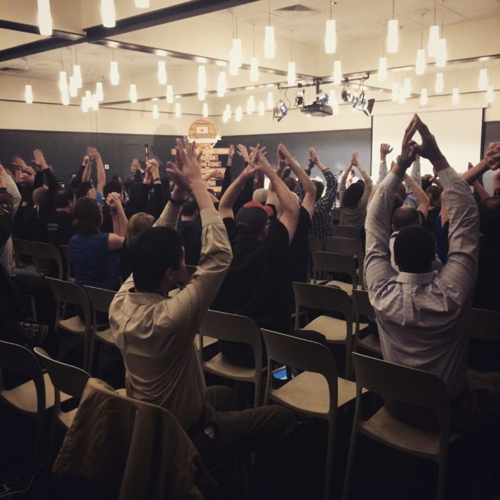 An audience stretching in their chairs before a seminar
