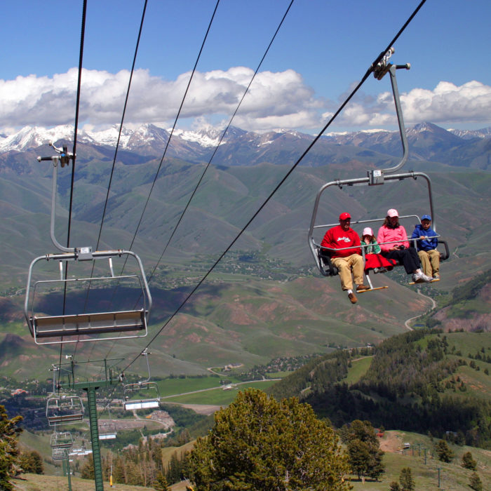 A chairlift going up a mountain in the summer.