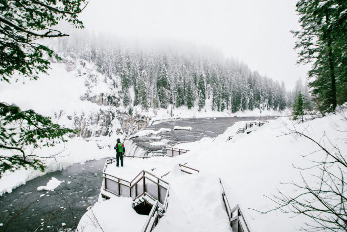 A man looking at a waterfall in the winter.