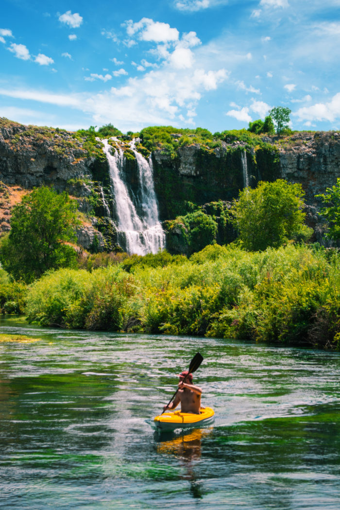 A man paddling a kayak at a spring.