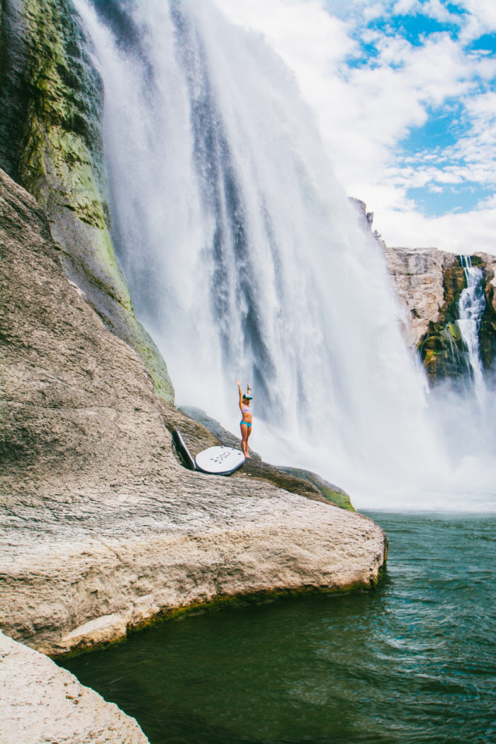 A woman standing beneath a towering waterfall.