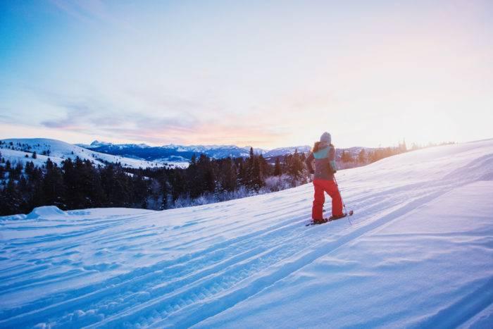 The sun rising as a hiker climbs a mountain in the snow.