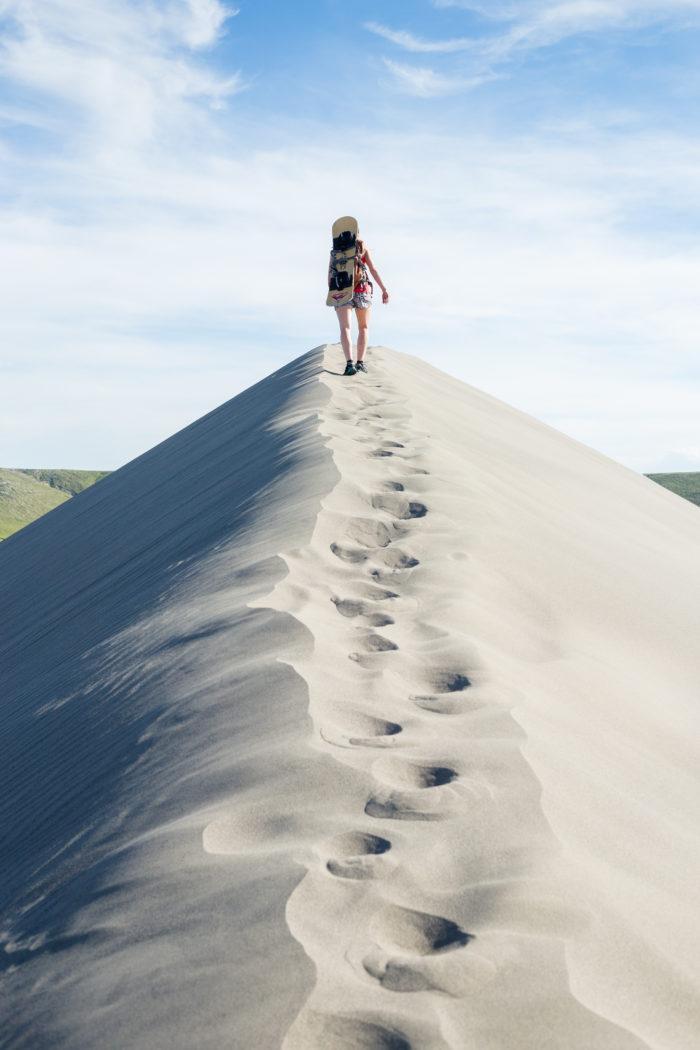 Woman hiking sand dune with sand board on her back.