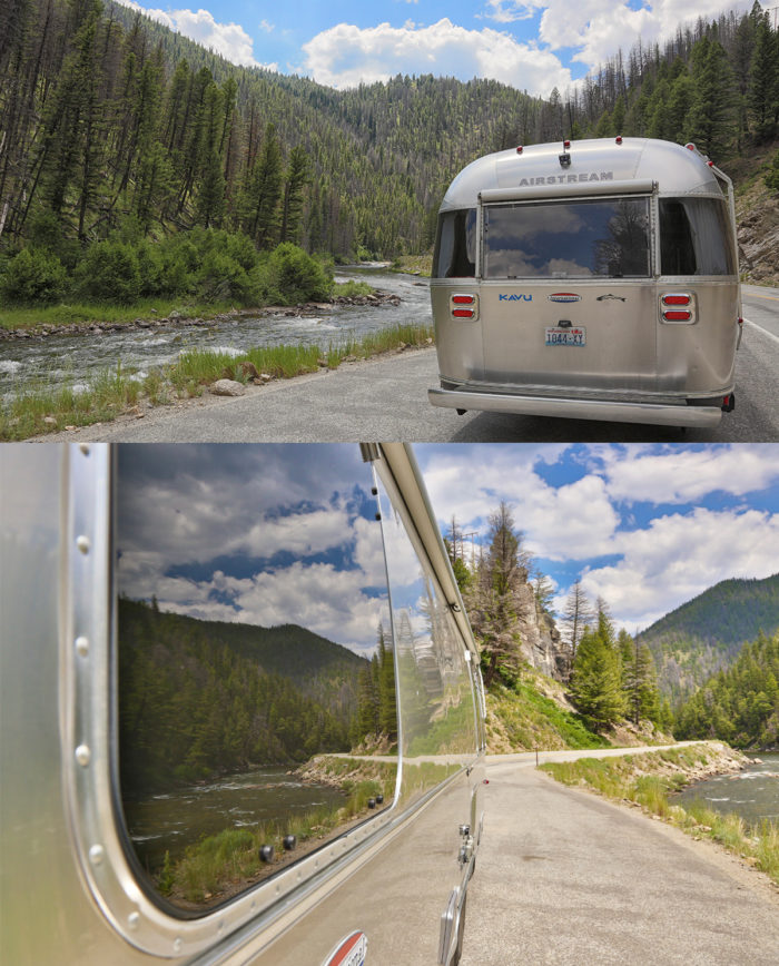 Airstream trailer along winding riverfront road.
