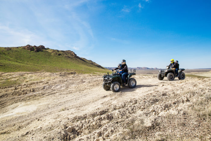 A family riding ATVs on a trail.