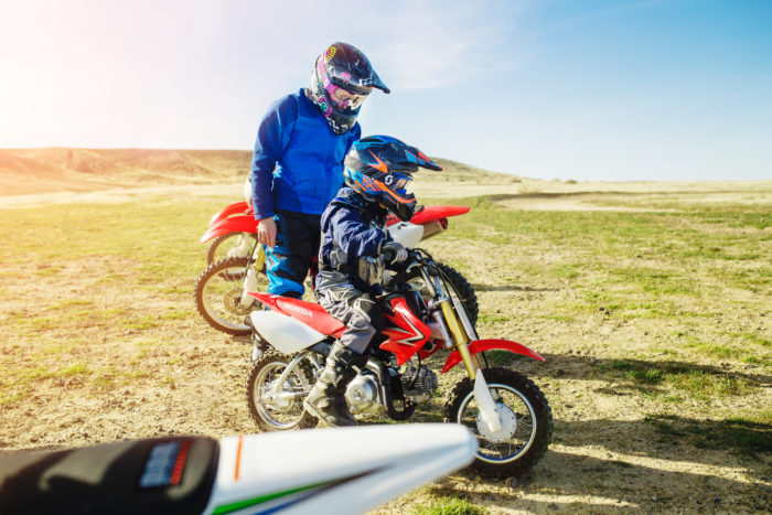 A father and son examining a dirt bike on a trail.