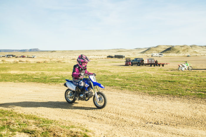 A young girl riding a dirt bike on a trail.