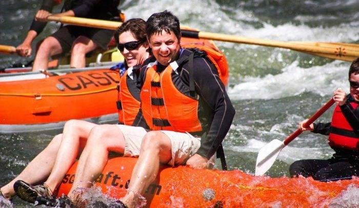A family enjoying a ride down a river on a raft.