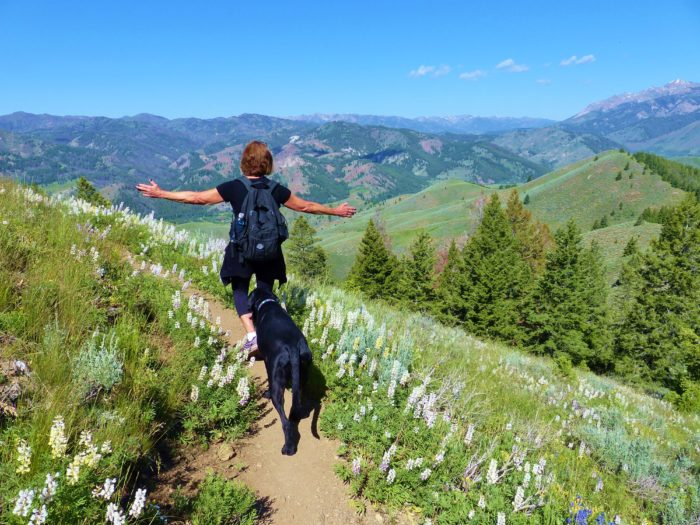 Woman hiking with dog.