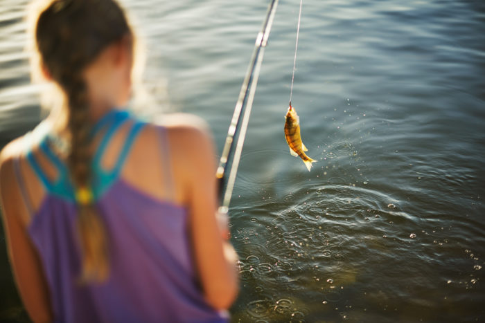 A girl reeling in a fish.