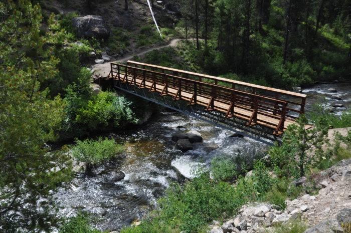 A bridge stretches over a mountain creek