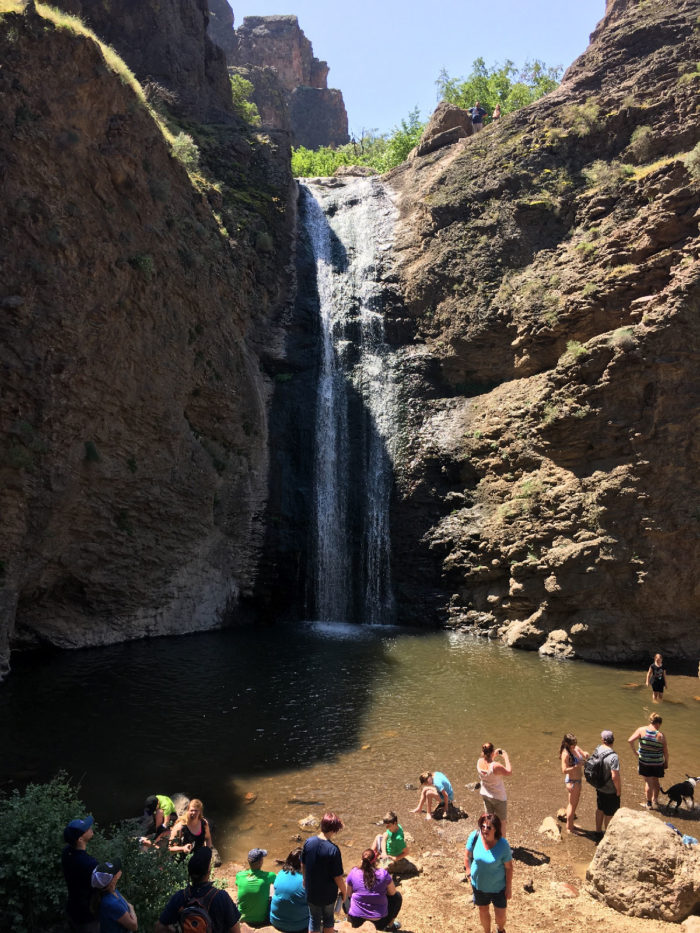 A group of people playing in the water at a waterfall.
