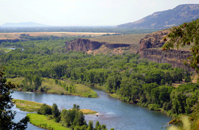 wide shot of river surrounded by trees and high cliffs.
