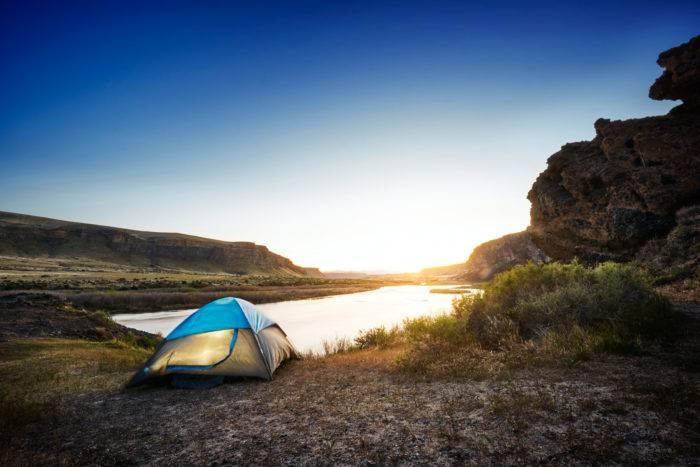 A tent set up along a river.