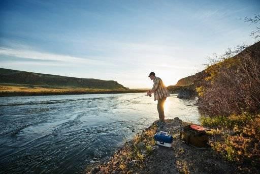 A man fishing along a river at sunset.