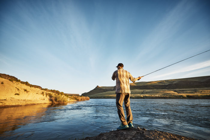 A man fishing along a river at sunset.
