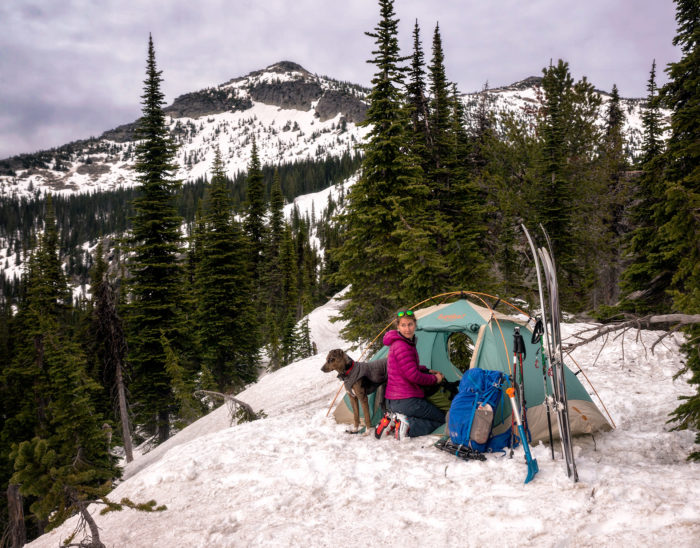 A woman and a dog sitting next to a tent in the snow on top of a mountain.