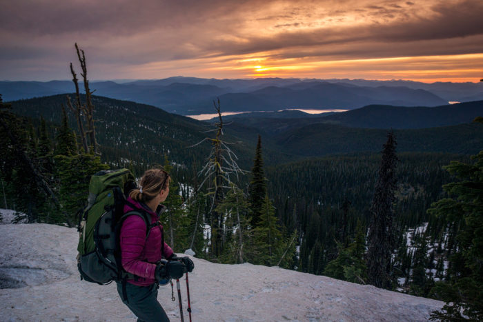 A hiker watches the sun set from the top of a snow covered mountain.