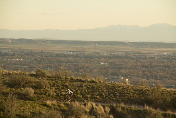 Mountain biker riding the foothills with Boise in background.