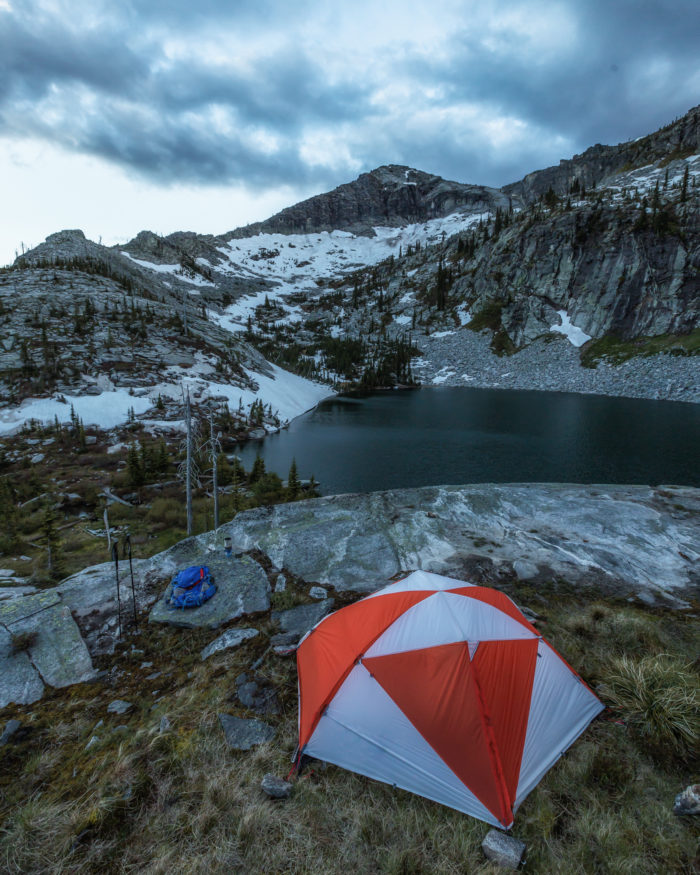 Tent on a rocky point above a mountain lake.