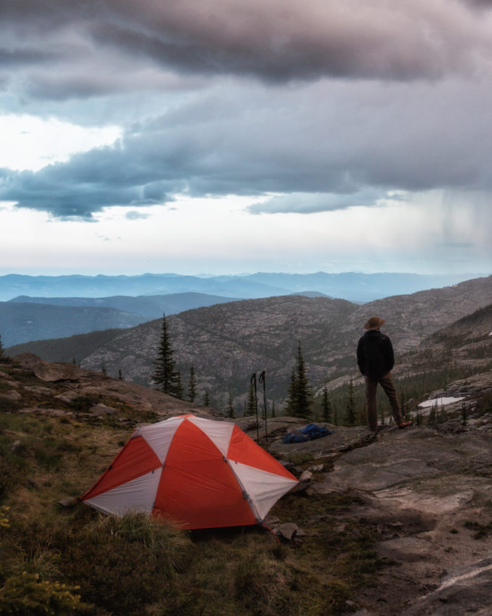 Man standing by tent looking at the mountains.
