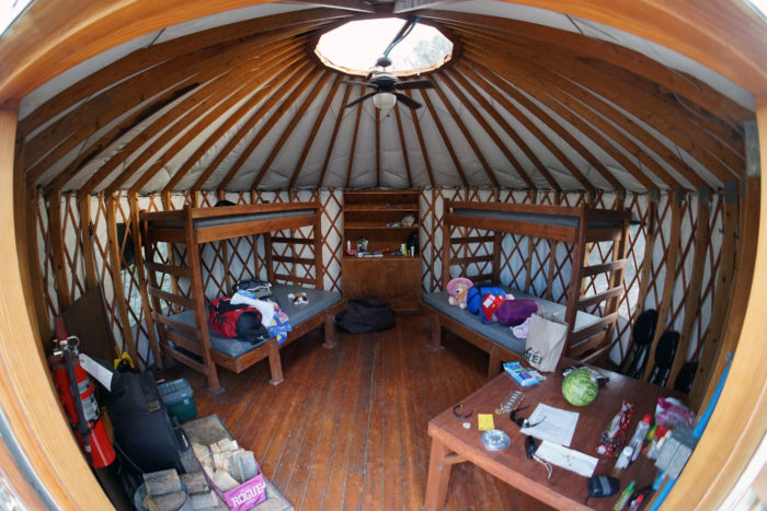 Interior of yurt with camping supplies.