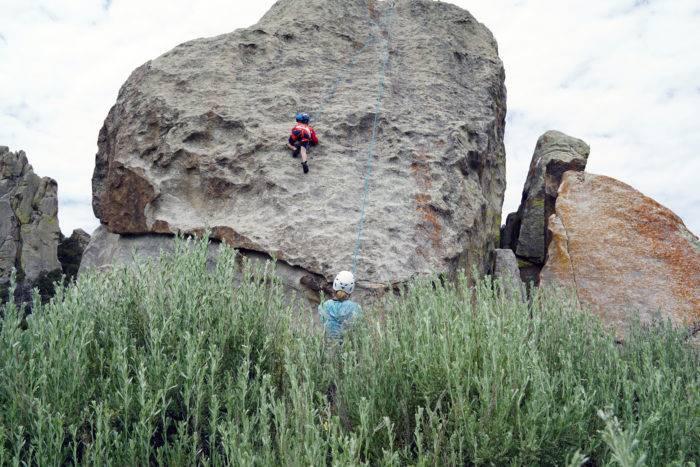 Young boy climbing a large rock in climbing gear