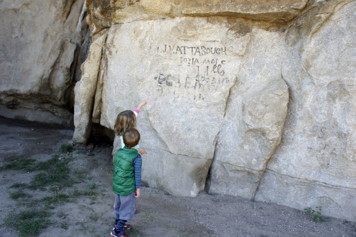 Kids point at names written on rock.