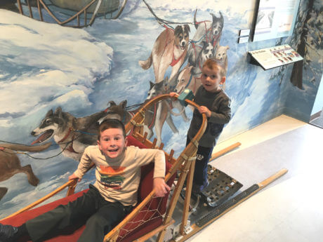 Two boys on a dog sled inside the Geotourism Center.