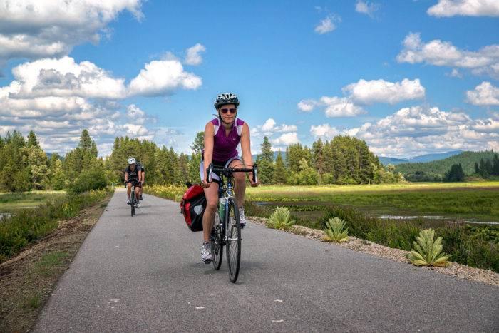 Cyclists riding next to a lake