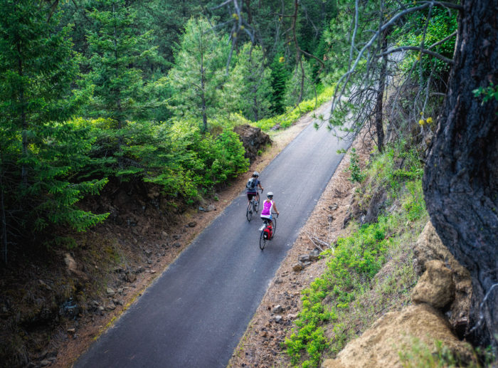 2 Cyclists riding on a paved path through the forest