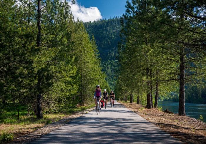 3 cyclists on a path near a lake.