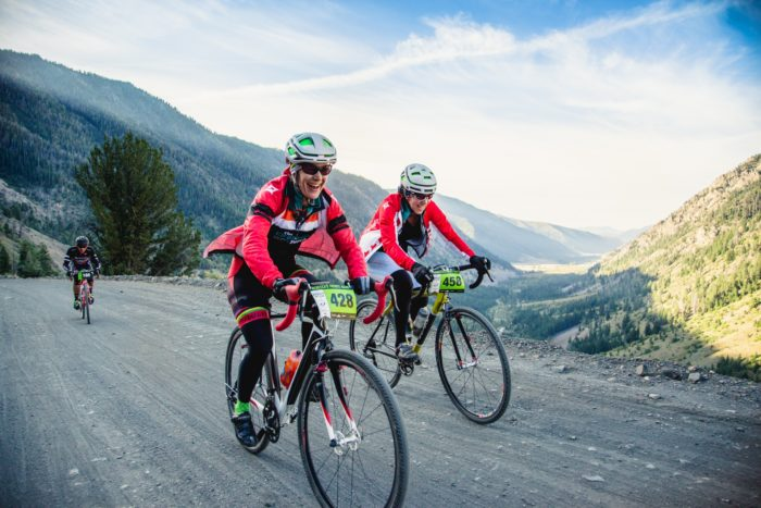 Two bikers ride along a gravel road surrounded by views of mountains and a valley below.
