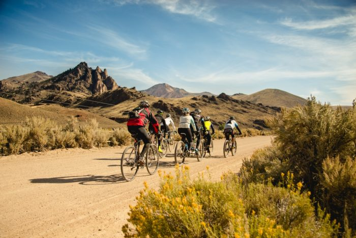 Rider group pedals along dirt road with mountains in the background.